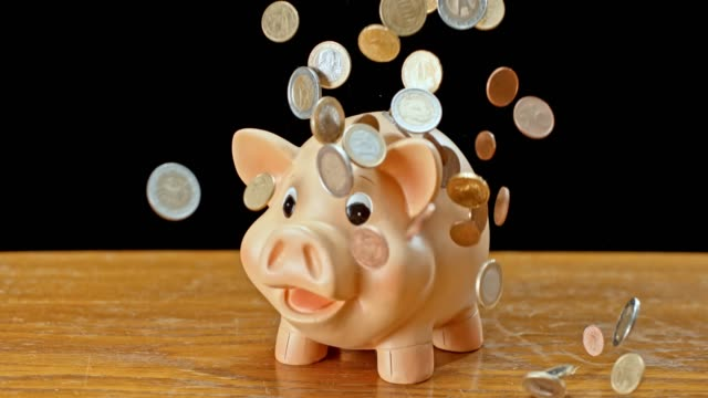 slo mo ld euro coins falling onto a piggy bank - european union coin stock videos & royalty-free footage