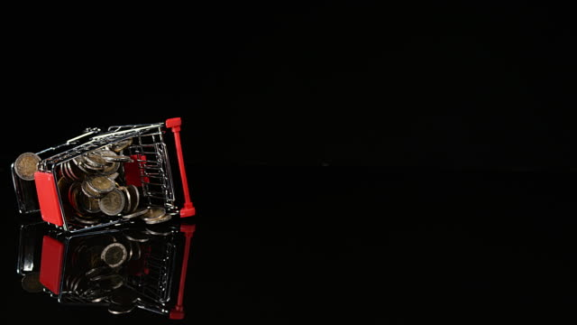 Euro Coins in Trolley rolling against Black Background, Slow motion, 4K