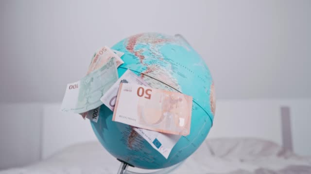 Euro currency notes falling over globe, super slow motion