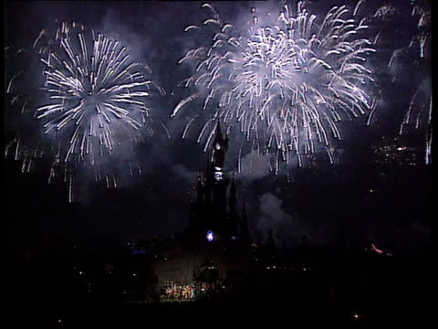 vídeos y material grabado en eventos de stock de dnao france paris gv fireworks explode next large castle in euro disney resort mickey mouse character on top of castle gv crowd of people enjoying... - castillo estructura de edificio