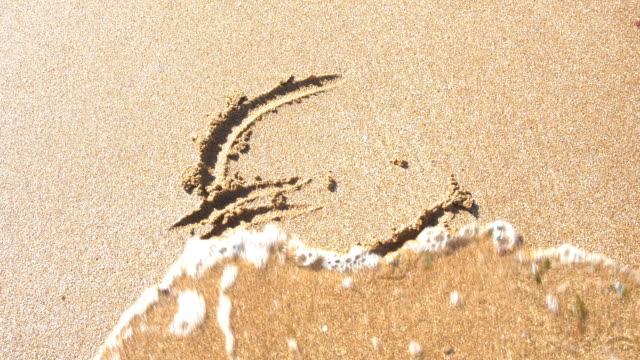 euro symbol in sand, washed away by the sea. - euro symbol stock videos and b-roll footage
