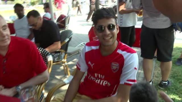 build-up to chelsea v arsenal; azerbaijan: baku: ext reporter to camera vox pops - arsenal fans wide shot of baku skyline and waterfront arsenal fans... - リチャード・パロット点の映像素材/bロール