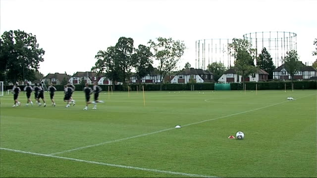 fulham fc training england london ext fullham players doing warmup exercises / martin jol watching team training / various general views fulham... - shooting at goal stock videos & royalty-free footage