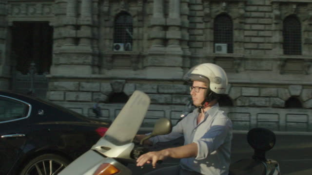 Europe, MAN ON VESPA motor scooter PASSES BY IN ROME TRAFFIC