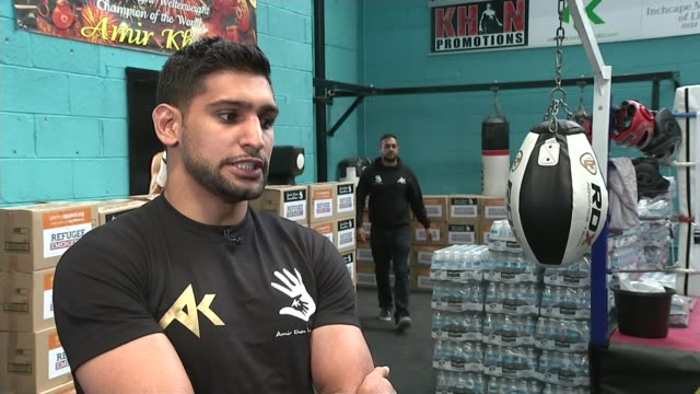 europe migrant crisis: boxer amir khan organises aid convoy for syrian refugees; england: lancashire: bolton: int men at boxing gym loading crates of... - box container video stock e b–roll