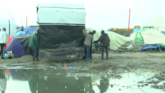 europe migrant crisis: calais 'jungle' camp site is littered with white asbestos; migrants moving makeshift tent along in camp pull out waterlogged... - アスベスト点の映像素材/bロール