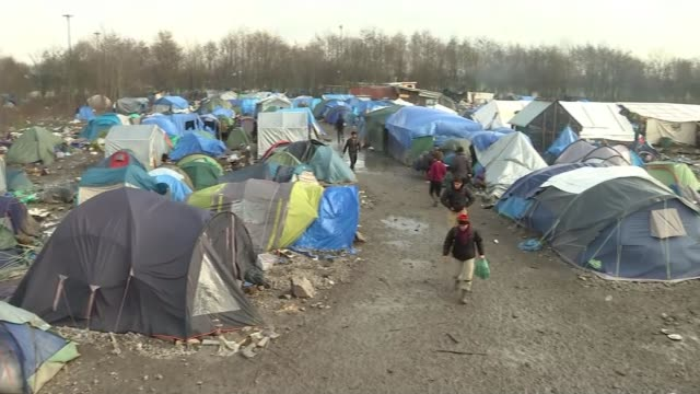 vidéos et rushes de europe migrant crisis: calais migrant camp given legal go-ahead to be cleared; migrant camp migrants eating in front of fire near tents little girl... - tente