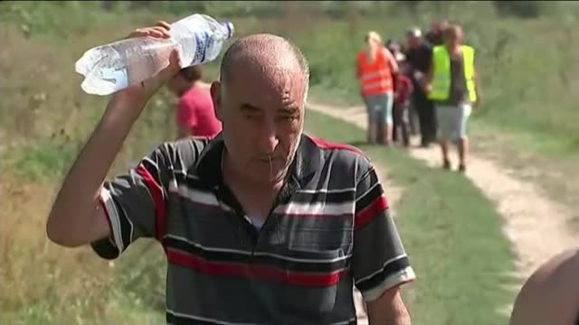 europe migrant crisis: croations bus refugees to hungarian border; croatia: tovarnik: elderly man - refugee - walking along as pourng water from... - croatia stock videos & royalty-free footage