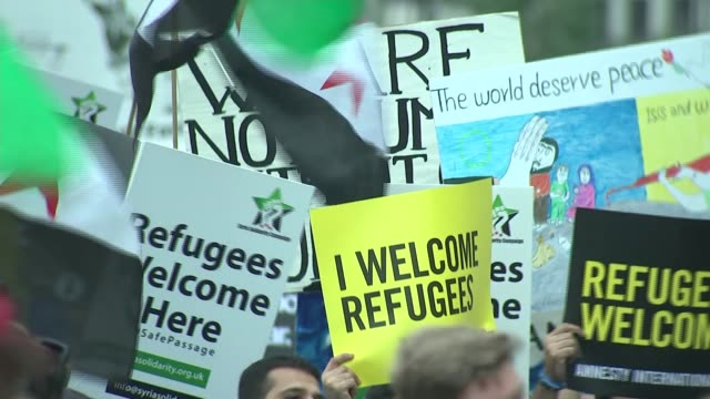 demonstration urges government to help refugees england london westminster ext wide shot protesters with large banner reading 'refugees welcome here'... - amnesty international stock videos & royalty-free footage