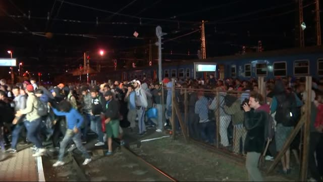 europe migrant crisis: european union agrees quota plan; austria: nickelsdorf: ext/night large crowd of refugees crossing railway tracks at station... - hungary stock videos & royalty-free footage