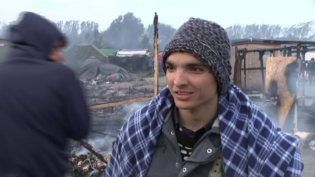 fires spread through calais jungle migrant camp amid clearance vox pop wide shot burnt out structures with caravans and tents under smoky sky pan - flüchtlingslager stock-videos und b-roll-filmmaterial