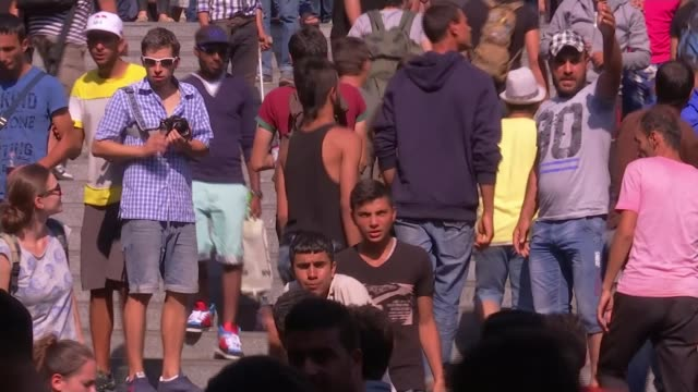 europe migrant crisis: government under pressure to do more; t02091504 hungary: budapest: ext migrants on steps oustide station migrant woman with... - budapest stock-videos und b-roll-filmmaterial