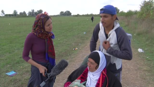 hungarian police try to control flow of migrants crossing from serbia various of syrian teenager pushing his mother along in wheelchair mother of... - hungarian culture stock videos & royalty-free footage
