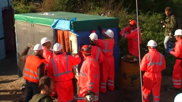 jungle camp begins to be dismantled in calais france calais ext various shots workers in hard hats and orange overalls dismantling jungle camp... - dismantling stock videos and b-roll footage