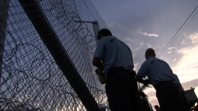 many eu countries impose border checks hungary police officers next to barbed wire fence at hungarian border with serbia silhouette of police officers - hungarian culture stock videos & royalty-free footage