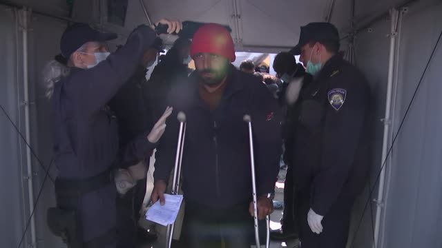 europe migrant crisis: migrant situation on the border into macedonia; male migrant on crutches being checked with metal detector by police officers... - セキュリティスキャナ点の映像素材/bロール