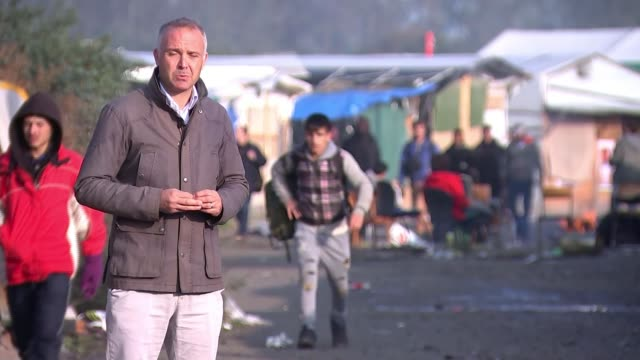 europe migrant crisis: more refugees leave jungle camp in calais; reporter to camera refugees along being monitored by police officers women wearing... - 僧衣点の映像素材/bロール