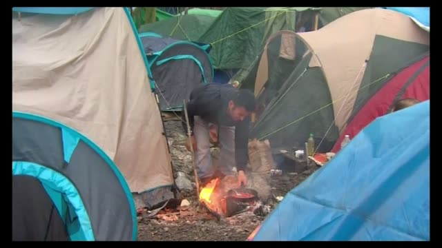 Numbers arriving set to top one million Conditions in Calais and Dunkirk Man cooking on fire between tents People sat around fire between tents of...