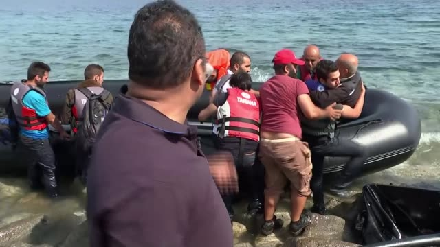 vídeos y material grabado en eventos de stock de europe migrant crisis: refugees contine to arrive on lesbos; reporter to camera [including reporter helping man with leg injury onto shore] - channel 4 news