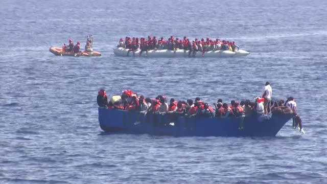 thousands continue to cross mediterranean sea in dangerous conditions mediterranean sea various shots migrants wearing orange life jackets as on... - flüchtling stock-videos und b-roll-filmmaterial