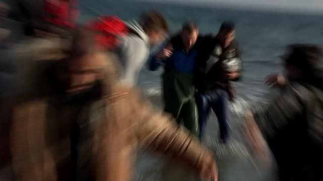 volunteers aid arriving refugees greece lesbos ext boatload of refugees and migrants waving as they approach the shore volunteer waving high viz bib... - wife carrying stock videos and b-roll footage