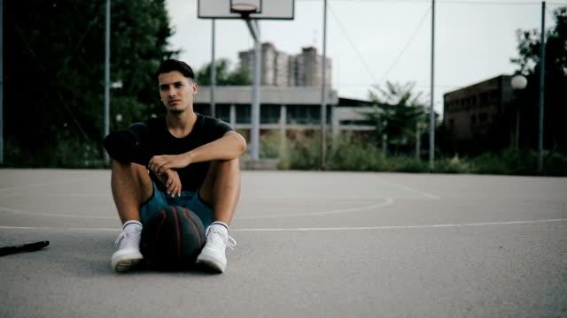 vídeos y material grabado en eventos de stock de atleta europeo tomando un descanso después de un partido de baloncesto - jugador de baloncesto
