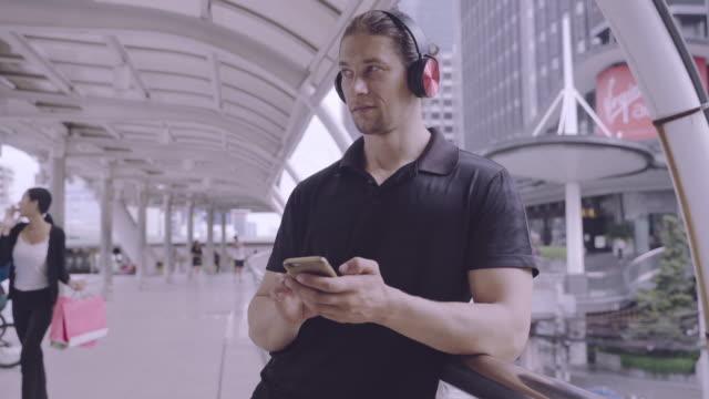 vídeos y material grabado en eventos de stock de hombres caucásicos europeos de entre 30 y 39 años, de pie, usando auriculares para escuchar música de mis aplicaciones de pc en el móvil era bien intencionado en el pasillo. - 30 39 years