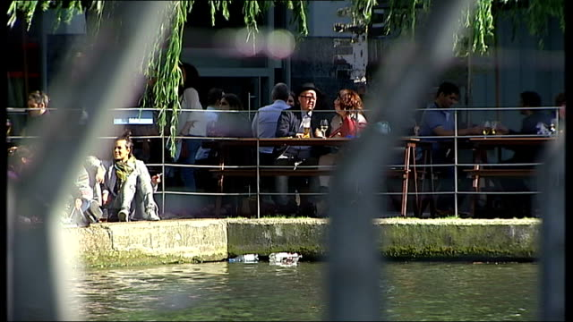European Central Bank introduces negative interest rate ENGLAND London Path along canal near Waterbus Stop Wide shot people sitting at outdoor cafe...