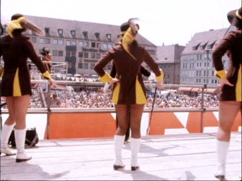 european election: rally in nuremberg; west germany: nuremberg: ext gv crowd at rally dutch dancers on stage french crepes prepared piece of waffle... - 西ドイツ点の映像素材/bロール