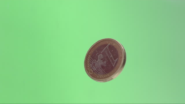 vídeos de stock, filmes e b-roll de european euro coin rotating infront of green screen - moeda