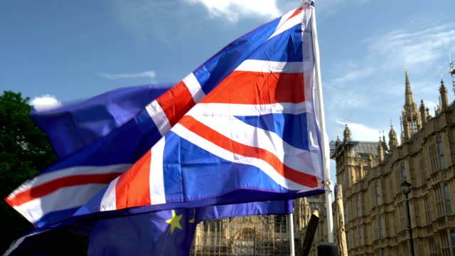 european flag with union jack in front of westminster - uk video stock e b–roll