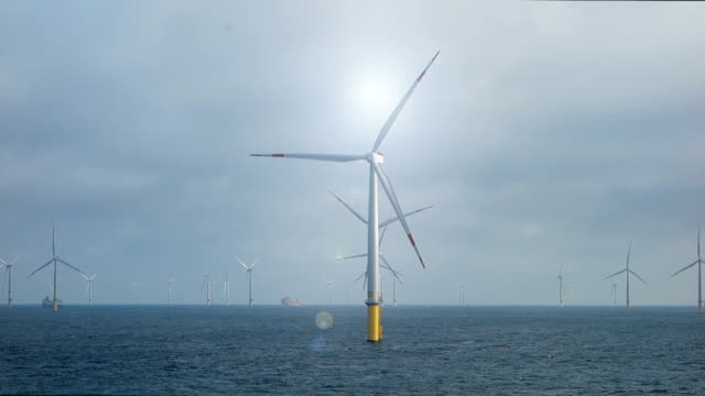 european offshore wind farm in full production with vessels in the back and sun above - north sea stock videos & royalty-free footage