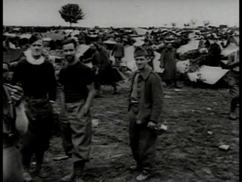 european soldiers walking on street ws german prison camp tents prisoners standing smoking prisoners around water trough prisoners on line for food... - prisoner of war stock videos & royalty-free footage