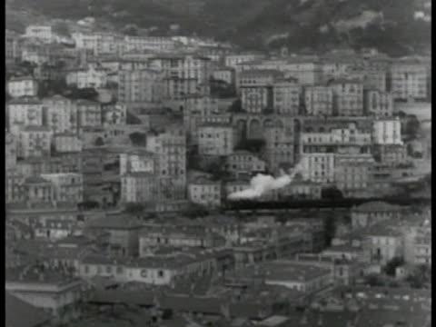 european train moving through unidentified hillside city. - テレビ番組点の映像素材/bロール