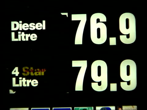 European Union action ITN ENGLAND London NIGHT CMS Petrol prices on board outside petrol station TILT BVs Drivers filling up cars at petrol station...