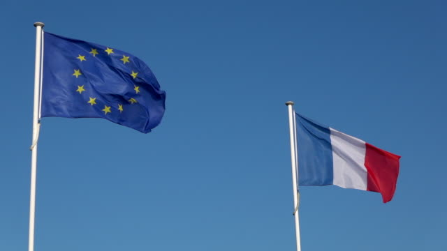 european union and french flag in wind - europa continente video stock e b–roll
