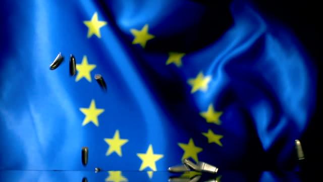 vídeos de stock e filmes b-roll de european union flag behind falling bullets - european union coin