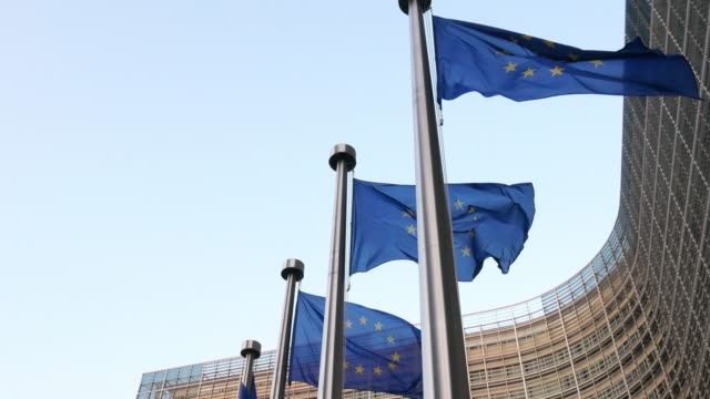 european union flags at berlaymont building - european commission building in brussels - regione di bruxelles capitale video stock e b–roll