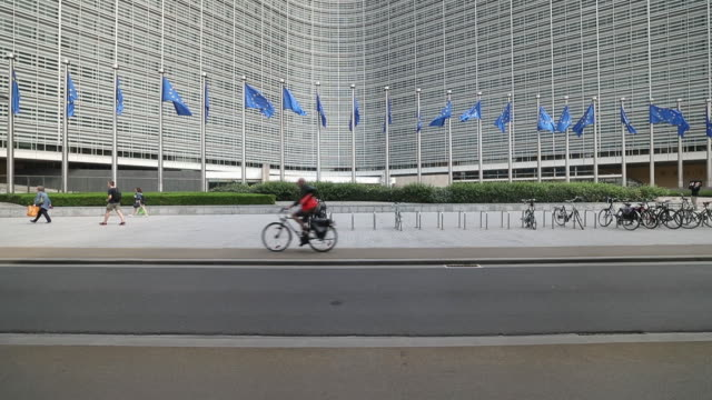 European Union flags fly in front of the European Commission Berlaymont building and he bronze statue 'Europe' stands outside European Union...