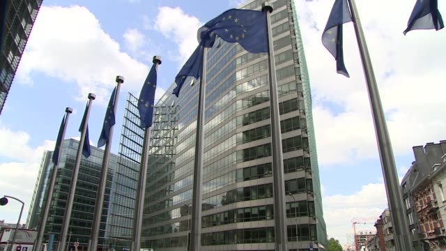 european union flags on poles in front of european commission building - europäische union stock-videos und b-roll-filmmaterial