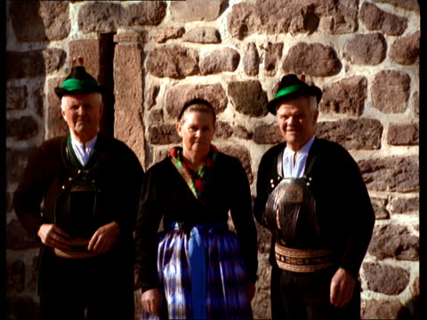 europeans wearing traditional alpine clothing stand in front of a stone house. - stone house stock videos & royalty-free footage