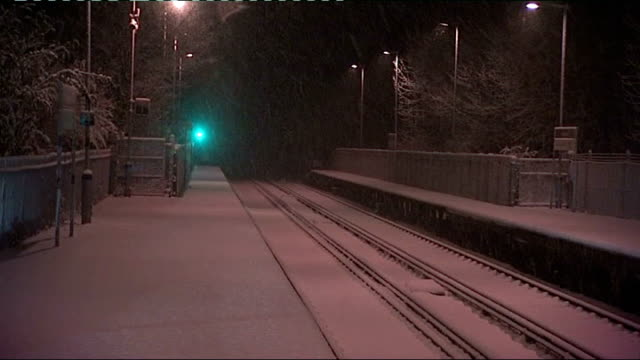 eurostar cancels services following train breakdowns location unknown snow falling on snowcovered station platform and railway line - eurostar stock-videos und b-roll-filmmaterial