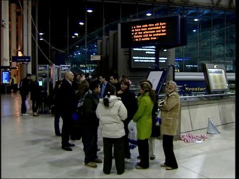 eurostar services resume following trackside fire england london waterloo international int passengers gathered round notice at eurostar terminal... - itv london tonight weekend stock videos & royalty-free footage
