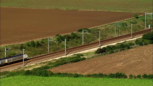 aerial eurostar train moving past farmland toward the channel tunnel/ pas-de-calais, france - anno 2006 video stock e b–roll