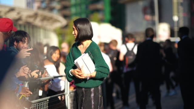 Eva Chen wears a green offshoulder top a black skirt yellow shoes during London Fashion Week September 2018 on September 17 2018 in London England