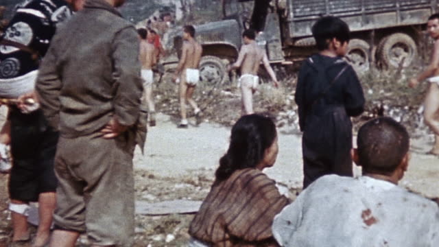evacuating civilians walking alongside stripped japanese prisoners of war who are being escorted down a road by marines during world war ii /... - guerra del pacifico video stock e b–roll