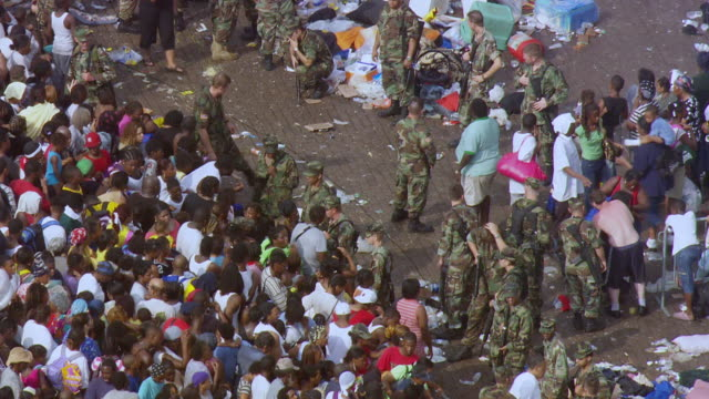 evacuees waiting for rescue help while military standing with weapons / united states - hurricane katrina stock videos and b-roll footage