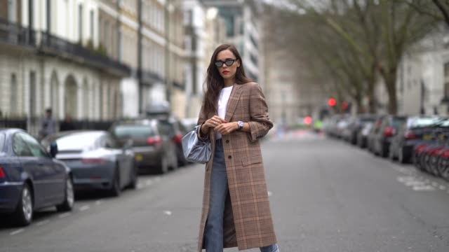 evangelie smyrniotaki wears a checked brown coat ripped jeans a blue bag a white top sunglasses during london fashion week february 2018 on february... - modewoche stock-videos und b-roll-filmmaterial
