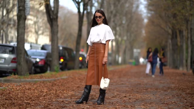 Evangelie Smyrniotaki wears a white top sunglasses brown pants black boots a white bag outside Issey Miyake during Paris Fashion Week Womenswear...