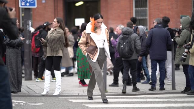 stockvideo's en b-roll-footage met evangelie smyrniotaki wears an earring made from orange and blue ostrich feathers a camel sheepskin jacket brown pants black pointy high heeled boots... - veer materiaal
